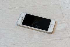 Lo smartphone rotto si trova sul primo piano bianco del pavimento immagini stock