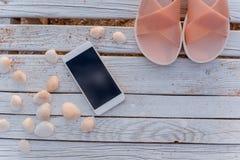Lo smartphone si trova nel circondare delle conchiglie sui bordi di legno fotografie stock libere da diritti