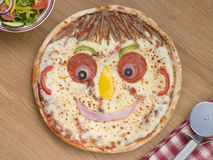 Lo smiley ha affrontato la pizza con un'insalata laterale Fotografia Stock