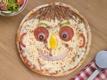 Lo smiley ha affrontato la pizza con un'insalata laterale Fotografia Stock