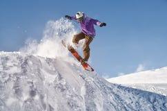 Lo snowboarder alla moda con il casco e la maschera salta dall'alto pendio della neve Immagine Stock