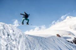 Lo snowboarder alla moda con il casco e la maschera salta dall'alto pendio della neve Immagine Stock Libera da Diritti