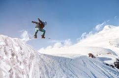Lo snowboarder alla moda con il casco e la maschera salta dall'alto pendio della neve Fotografie Stock