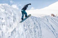 Lo snowboarder alla moda con il casco e la maschera salta dall'alto pendio della neve Fotografie Stock Libere da Diritti