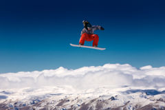 Lo Snowboarder che salta in aria fotografia stock libera da diritti