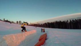 Lo Snowboarder che salta attraverso l'aria con cielo blu profondo nel fondo Snowboarder in volo Snowboard che salta nel livello archivi video