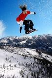 Lo Snowboarder che salta contro il cielo blu Fotografia Stock