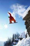Lo Snowboarder che salta contro il cielo blu Fotografie Stock