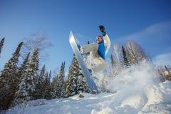 Lo Snowboarder che salta dal trampolino contro il cielo Immagine Stock Libera da Diritti