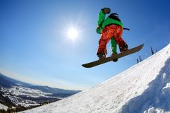 Lo Snowboarder che salta dal trampolino contro il cielo Immagini Stock