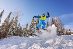 Lo Snowboarder che salta dal trampolino contro il cielo immagine stock