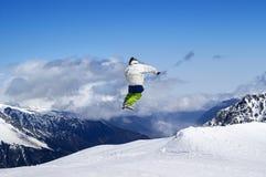 Lo Snowboarder che salta nel parco del terreno alla stazione sciistica sull'inverno del sole fotografie stock