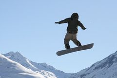 Lo Snowboarder che salta su nell'aria Fotografie Stock
