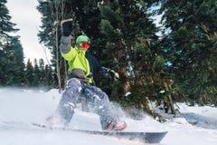 Lo Snowboarder con attrezzatura speciale sta guidando e rallentamento nella foresta della montagna immagine stock libera da diritti