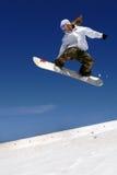 Lo snowboarder della donna salta il pendio Immagine Stock