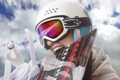 Lo snowboarder della ragazza in casco e negli occhiali di protezione morde lo snowboard Fotografie Stock Libere da Diritti