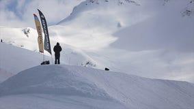 Lo Snowboarder fa il salto in alto dal trampolino, giro sul pendio MONTAGNE NEVOSE archivi video