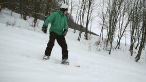 Lo Snowboarder fa scorrere il pendio della neve video d archivio