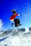 Lo Snowboarder fa un salto immagine stock