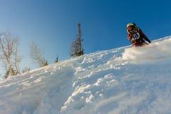 Lo snowboarder Freerider della ragazza fa scorrere dalla montagna alla luce Fotografie Stock Libere da Diritti