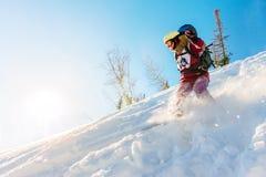 Lo snowboarder Freerider della ragazza fa scorrere dalla montagna alla luce Immagine Stock