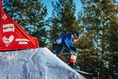 Lo snowboarder maschio dell'atleta del primo piano salta da un trampolino Fotografia Stock