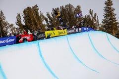 Lo Snowboarder ottiene l'attenzione dalla folla degli spettatori alla concorrenza del mezzo tubo, Mammoth Mountain, la California Immagine Stock
