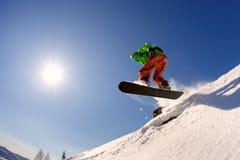 Lo snowboarder salta dal trampolino contro il cielo blu Fotografia Stock