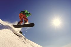 Lo snowboarder salta dal trampolino contro il cielo blu immagini stock
