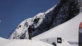 Lo Snowboarder salta dal trampolino fa parecchie vibrazioni complete in aria Montagne della neve del paesaggio Cielo blu video d archivio