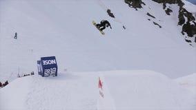 Lo Snowboarder salta dal trampolino fa parecchie vibrazioni, tiene il bordo in aria estremo archivi video