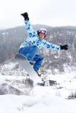 Lo Snowboarder salta sullo snowboard Fotografia Stock