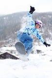 Lo snowboarder sorridente salta sullo snowboard sulla montagna Immagini Stock