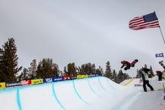 Lo Snowboarder vola dal mezzo tubo durante la concorrenza, Mammoth Mountain, la California U.S.A. Immagine Stock