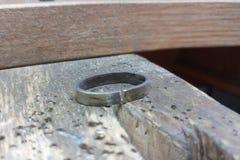 Lo spazio in bianco dell'anello di oro bianco si trova su una superficie di lavoro di legno Il processo di fabbricazione dei gioi immagine stock libera da diritti