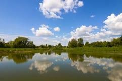Lo specchio del lago gradisce con cielo blu drammatico con le nuvole fotografia stock