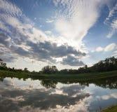 Lo specchio del lago gradisce con le nuvole drammatiche del cielo blu immagine stock libera da diritti