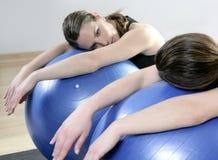 Lo specchio di Aerobics si distende la sfera di stabilità dei pilates della donna Immagini Stock