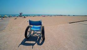 Lo speciale ha fuso la sedia a rotelle sulla spiaggia sabbiosa della stazione turistica Fotografie Stock
