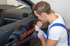 Lo specialista marcante a caldo dell'automobile mette il logo con l'automobile che avvolge il film sull'automobile immagini stock
