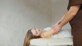 Lo specialista maschio medico con esperienza con i movimenti delicati passa il massaggio per la ragazza al paziente, che si trova video d archivio