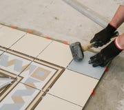 Lo specialista per la stenditura delle mattonelle allinea le mattonelle con un ` s del carpentiere Immagine Stock Libera da Diritti