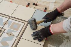 Lo specialista per la stenditura delle mattonelle allinea le mattonelle con un ` s del carpentiere Fotografie Stock