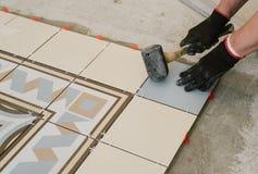 Lo specialista per la stenditura delle mattonelle allinea le mattonelle con un ` s del carpentiere Fotografie Stock Libere da Diritti
