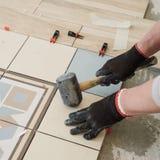 Lo specialista per la stenditura delle mattonelle allinea le mattonelle con un ` s del carpentiere Immagini Stock