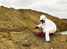 Lo specialista in vestiario di protezione preleva un campione del suolo dentro Fotografia Stock