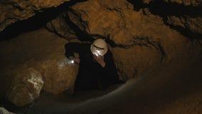 Lo speleologo trova e va nel passaggio nella caverna 4K video d archivio