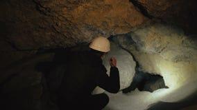 Lo speleologo trova e va nel passaggio nella caverna 4K archivi video
