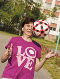 Lo sport della donna anziana prova entusiasta a prendere la palla gettata a lei Gioco del gioco del calcio fotografie stock