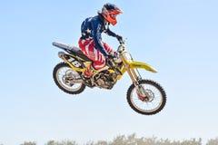 Lo sportivo di volo su un motocross bike sul trampolino Immagini Stock